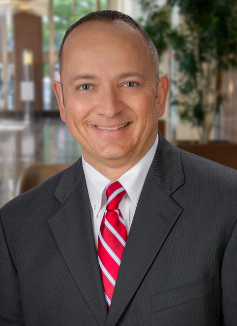 man in suit with red tie looking at camera